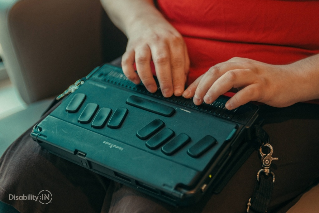 A person using a braille display on their lap